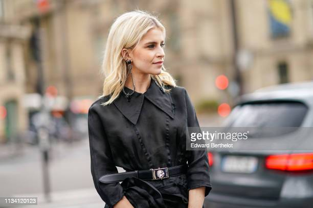 Caroline Daur wears earrings a black dress a black Miu Miu belt outside Miu Miu during Paris Fashion Week Womenswear Fall/Winter 2019/2020 on March...