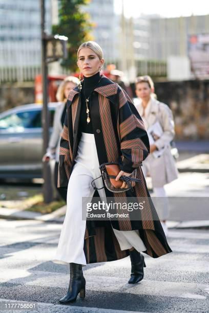 Caroline Daur wears earrings, a necklace, a black and colorful striped oversized coat, a Loewe handbag,a black turtleneck, white high waist wide-legs...