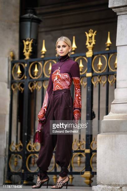 Caroline Daur wears earrings, a necklace, a plum-color turtleneck with rust-color and white pattern print, a burgundy bag, dark brown pants, black...