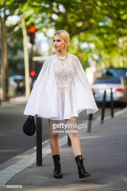 Caroline Daur wears earrings, a necklace, a white ruffled lace mesh dress, black boots, a black bag, outside Giambattista Valli, during Paris Fashion...