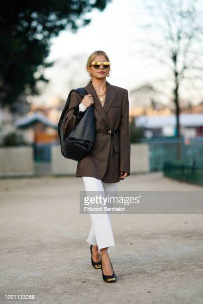 Caroline Daur wears earrings, mirrored sunglasses, necklaces, a brown jacket, white crop ripped hem pants, black quilted shoes with gold-tone tips, a...