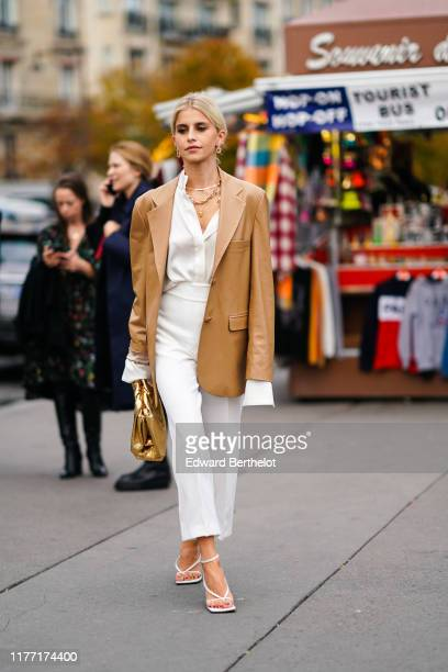 Caroline Daur wears earrings necklaces a camel leather oversized jacket a white shirt white widelegs pants white sandals a shiny gold puff bag...