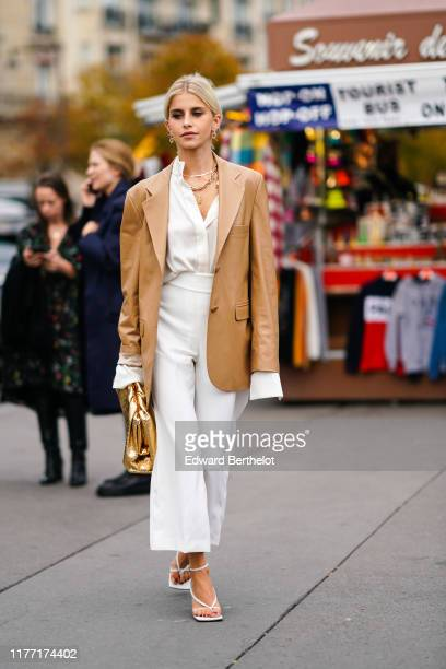 Caroline Daur wears earrings, necklaces, a camel leather oversized jacket, a white shirt, white wide-legs pants, white sandals, a shiny gold puff...