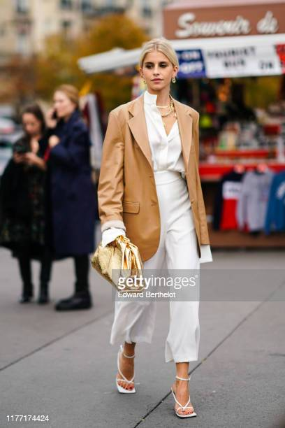 Caroline Daur wears earrings necklaces a camel leather oversized jacket a white shirt white widelegs crop pants white sandals a shiny gold puff bag...