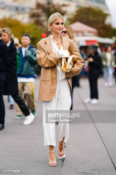 Caroline Daur wears earrings, necklaces, a camel leather oversized jacket, a white shirt, white wide-legs crop pants, white sandals, a shiny gold...