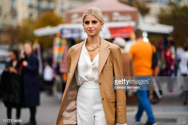 Caroline Daur wears earrings, necklaces, a camel leather oversized jacket, a white shirt, white pants, outside Rochas, during Paris Fashion Week -...