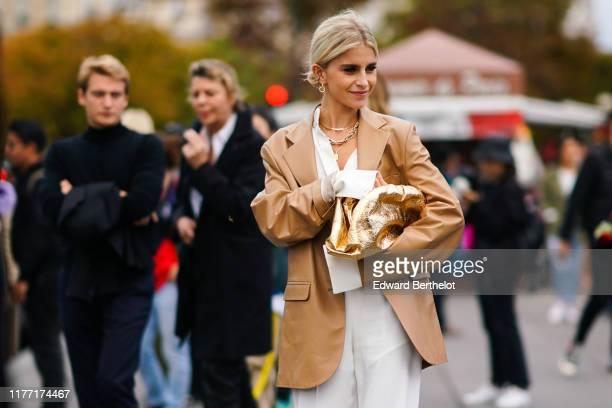 Caroline Daur wears earrings, necklaces, a camel leather oversized jacket, a white shirt, white pants, a shiny gold puff bag, outside Rochas, during...