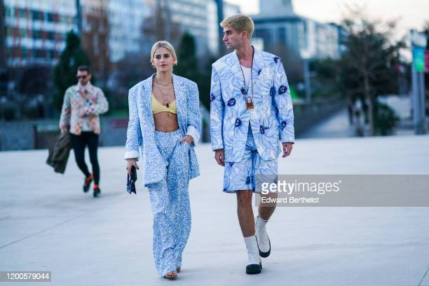 Caroline Daur wears earrings necklaces rings a bracelet a yellow bra top a white and light blue floral print oversized jacket white and light blue...