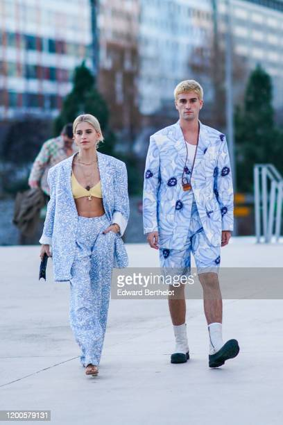 Caroline Daur wears earrings, necklaces, rings, a bracelet, a yellow bra top, a white and light blue floral print oversized jacket, white and light...