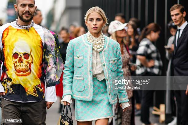 Caroline Daur wears earrings pearl necklaces a Gucci white top a light green Gucci jacket an assorted mini skirt a yellow and black handbag outside...