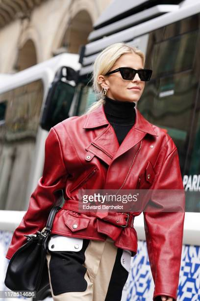 Caroline Daur wears earrings, Saint Laurent sunglasses, a black turtleneck, a red leather jacket, a black bag, cream-color pants with dark brown...