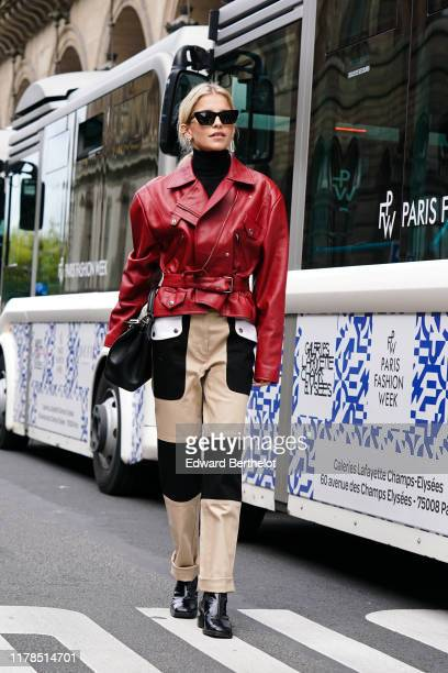 Caroline Daur wears earrings, Saint Laurent sunglasses, a black turtleneck, a red leather jacket, a black bag, cream-color rolled-up hem pants with...