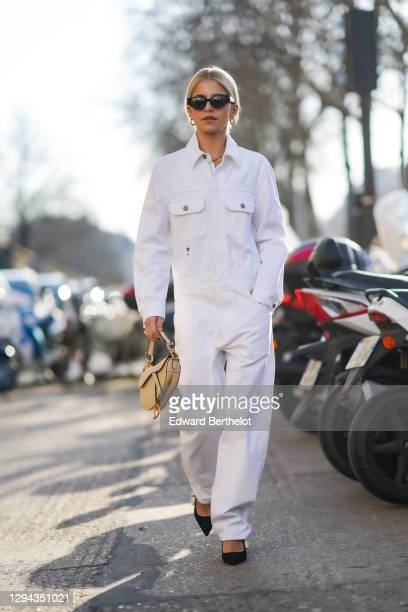 Caroline Daur wears earrings, sunglasses, a white Dior denim jumpsuit, a beige Dior saddle bag, black J'Adior pumps, outside Dior, during Paris...