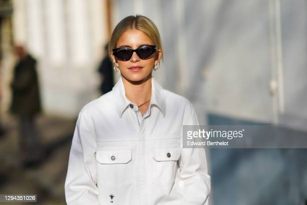 Caroline Daur wears earrings, sunglasses, a white Dior denim top, outside Dior, during Paris Fashion Week - Haute Couture Spring/Summer 2020, on...