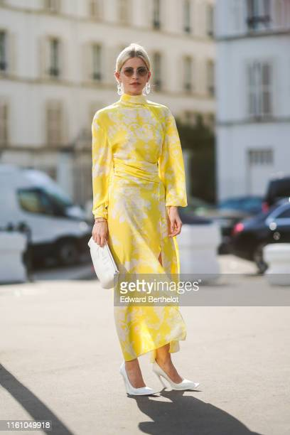 Caroline Daur wears earrings, sunglasses, a yellow and white dress, a white bag, white shoes, outside Acne, during Paris Fashion Week - Haute Couture...