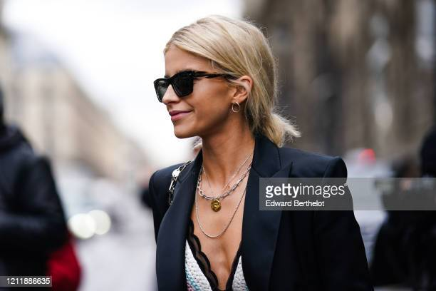 Caroline Daur wears earrings, sunglasses, necklaces, a white crochet bra with a scalloped black trim, a lustrous black jacket, outside Giambattista...