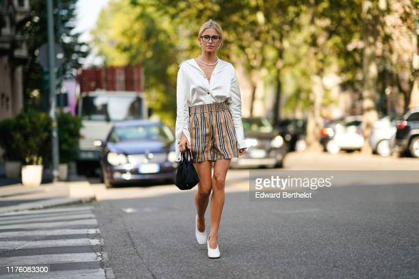 Caroline Daur wears glasses, a pearl beaded necklace, a white open shirt, a brown black and red striped sorts, white shoes, a black bag, outside the...