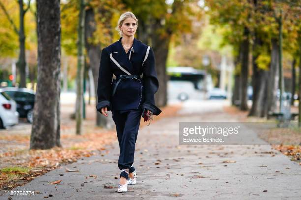 Caroline Daur wears necklaces, a navy blue oversized jacket with apparent seams and ripped hem white inserts, a black belt, a red mini bag, navy blue...