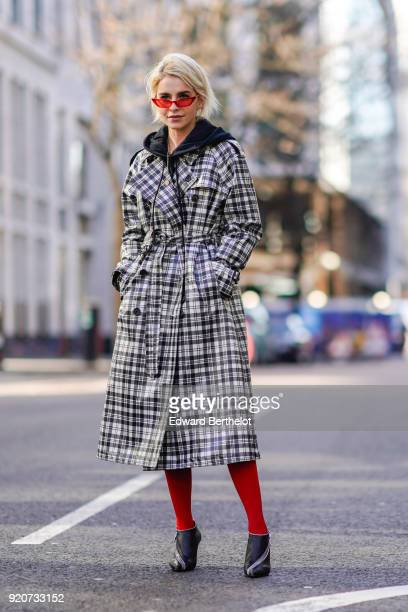 Caroline Daur wears red sunglasses a checked trench coat red tights shoes during London Fashion Week February 2018 on February 17 2018 in London...