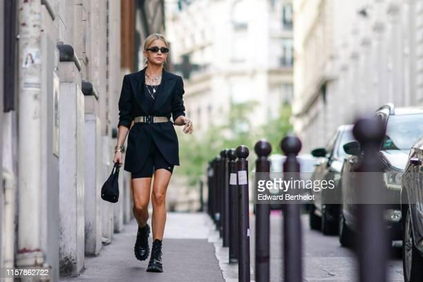 Caroline Daur wears sunglasses a black blazer jacket a belt a necklace jewelry black shorts a bag leather shoes outside Alyx during Paris Fashion...