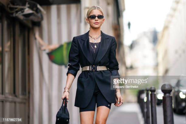 Caroline Daur wears sunglasses a black blazer jacket a belt a necklace jewelry black shorts a bag leather shoes outside Alyx during Paris Fashion...