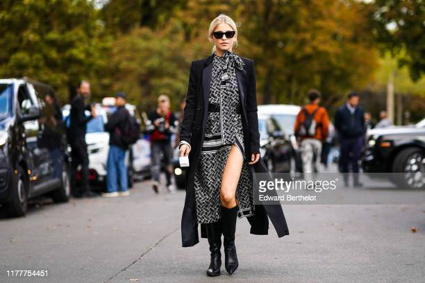 Caroline Daur wears sunglasses a black long coat a black and white side slit dress with printed geometric patterns a scarf black leather boots...