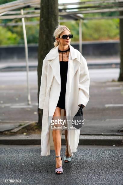 Caroline Daur wears sunglasses, a black mini dress, a white sides-slit coat, a black bag, glittering bejeweled heeled sandals, outside Alessandra...