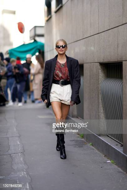 Caroline Daur wears sunglasses, a black oversized blazer jacket, a clutch, a red floral print top, a belt with metallic buckle, a white short, black...