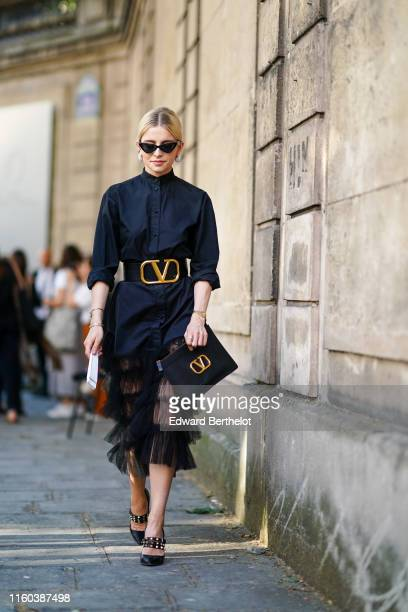 Caroline Daur wears sunglasses a black shirt dress with a lace mesh ruffled part a large leather belt a Valentino logo clutch studded shoes outside...