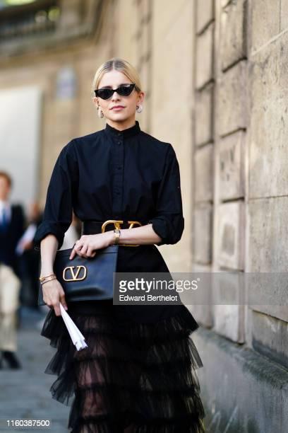 Caroline Daur wears sunglasses, a black shirt dress with a lace mesh ruffled part, a large leather belt, a Valentino logo clutch, studded shoes,...