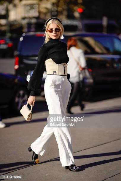 Caroline Daur wears sunglasses a black top white corset white flare pants a bag outside Rochas during Paris Fashion Week Womenswear Spring/Summer...