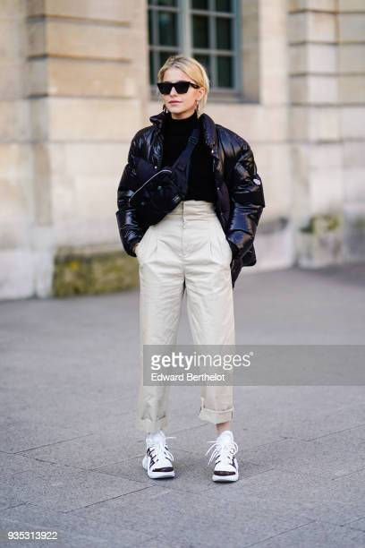 Caroline Daur wears sunglasses a black turtleneck a glossy black vinyl puffy jacket offwhite pleated waist cuffed pants black and white sneakers a...