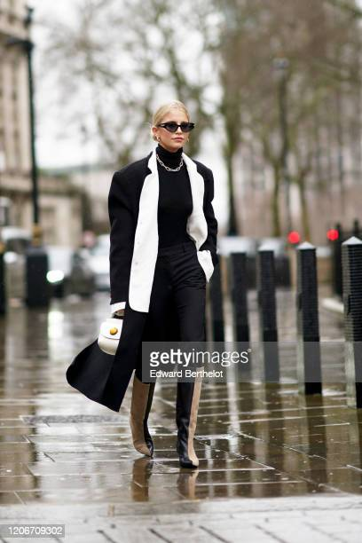 Caroline Daur wears sunglasses a black turtleneck pullover a chain metallic necklace a black long coat with white collar a white bag beige and black...
