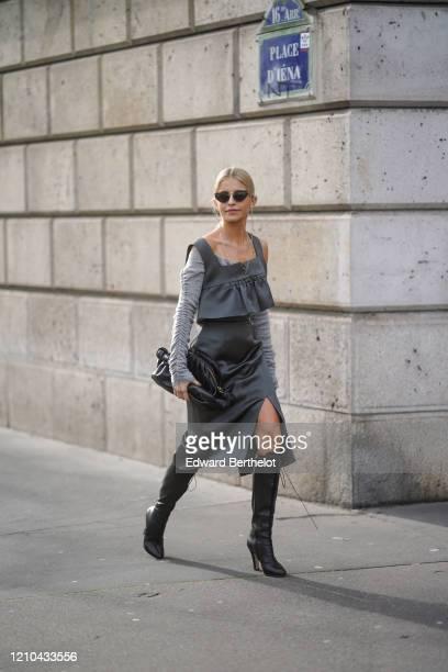 Caroline Daur wears sunglasses, a Bottega Veneta black leather bag, a gray wool pullover, a gray ruffled dress, black leather pointy boots, outside...