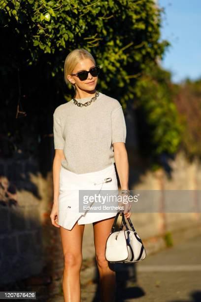 Caroline Daur wears sunglasses, a chain necklace, a gray top, a white mini skirt, black boots, a Prada bag, outside Prada, during Milan Fashion Week...