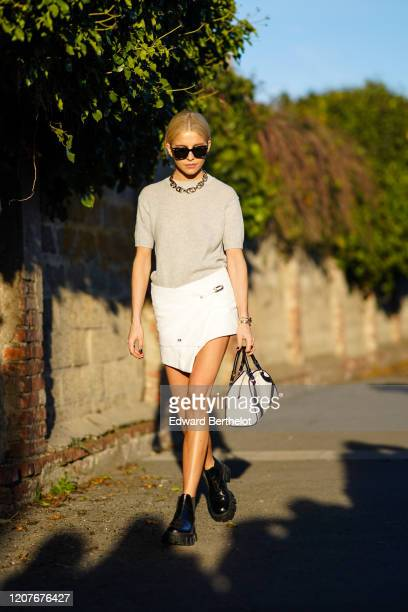 Caroline Daur wears sunglasses, a chain necklace, a gray top, a white mini skirt, black boots, a Prada bag, outside Prada, during Milan Fashion Week...
