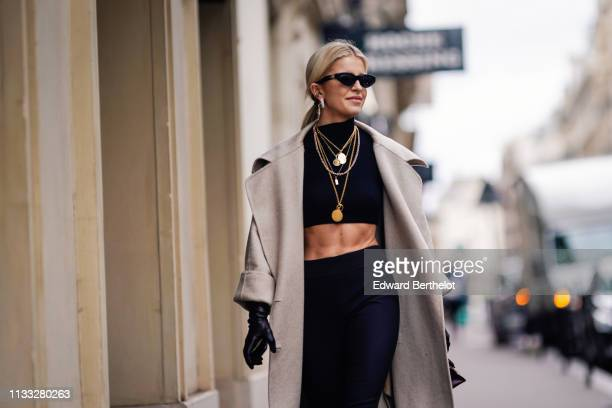 Caroline Daur wears sunglasses, a gray long coat, a black crop top, dark pants, several necklaces, earrings, outside Elie Saab, during Paris Fashion...