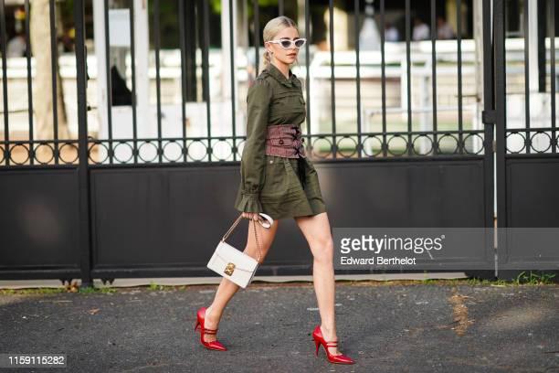 Caroline Daur wears sunglasses, a green khaki dress with a corset, a white bag, red shoes, earrings, outside Miu Miu Club 2020, on June 29, 2019 in...