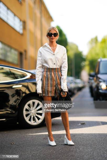 Caroline Daur wears sunglasses a pearl beaded necklace a white open shirt a brown black and red striped shorts a black bag white shoes outside the...