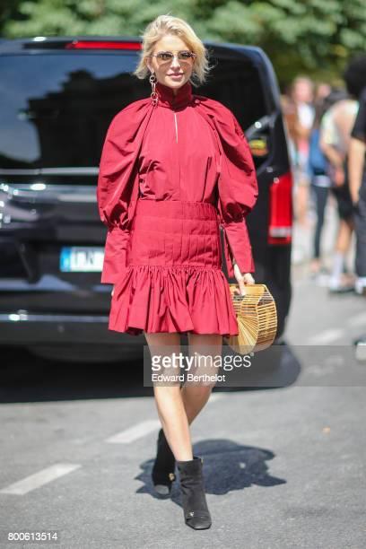 Caroline Daur wears sunglasses a red dress a semi circular bag and black shoes outside the Dior show during Paris Fashion Week Menswear Spring/Summer...
