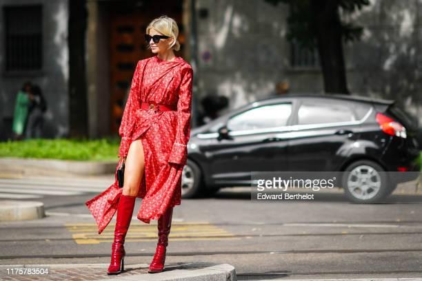 Caroline Daur wears sunglasses, a red dress with printed Fendi logos, a Fendi black bag, red shiny high heeled boots, a belt, outside the Fendi show...