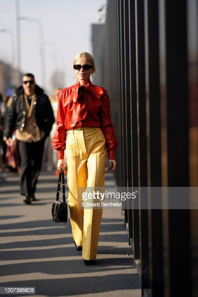 Caroline Daur wears sunglasses, a red leather shirt, yellow leather pants, a bag, earrings, outside Gucci, during Milan Fashion Week Fall/Winter...