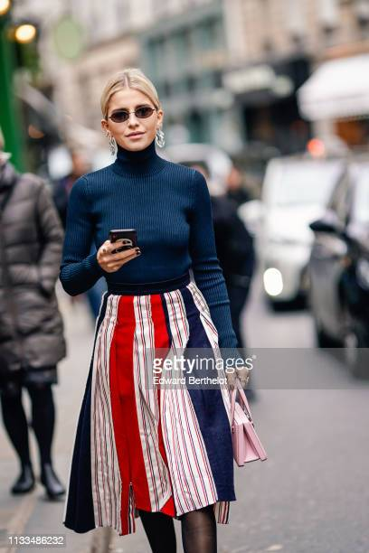 Caroline Daur wears sunglasses a turtleneck top earrings a red striped skirt black leather shoes a pink bag outside Thom Browne during Paris Fashion...