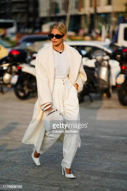 Caroline Daur wears sunglasses a white coat a white bag a white tshirt pants heels shoes outside the Alberta Ferretti show during Milan Fashion Week...