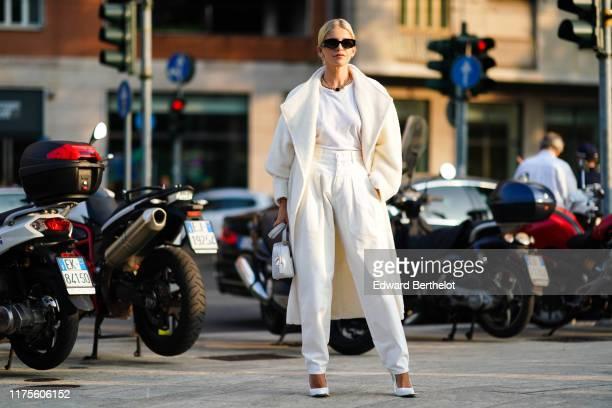 Caroline Daur wears sunglasses, a white coat, a white bag, a white t-shirt, pants, heels shoes, outside the Alberta Ferretti show during Milan...