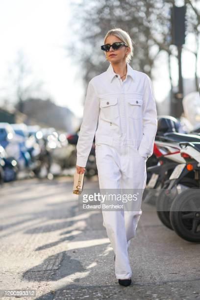 Caroline Daur wears sunglasses a white denim jumpsuit a Dior Saddle bag outside Dior during Paris Fashion Week Haute Couture Spring/Summer 2020 on...