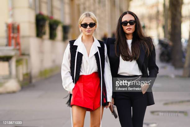Caroline Daur wears sunglasses, a white shirt, a black sleeveless embroidered jacket, red shorts, ; Evangelie Smyrniotaki wears sunglasses, a black...