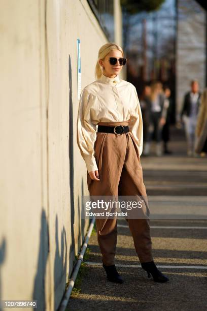 Caroline Daur wears sunglasses, a white shirt, a leather belt, brown pants, a bag, outside Alberta Ferretti, during Milan Fashion Week Fall/Winter...