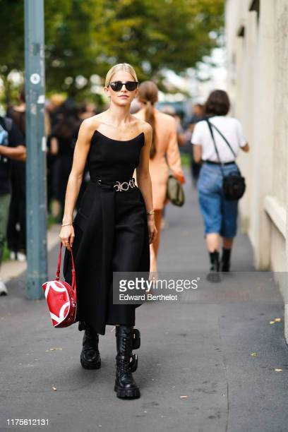 Caroline Daur wears sunglasses an offshoulder dress a red bag outside the Prada show during Milan Fashion Week Spring/Summer 2020 on September 18...