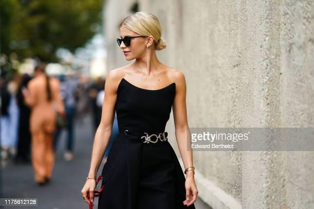 Caroline Daur wears sunglasses, an off-shoulder dress, outside the Prada show during Milan Fashion Week Spring/Summer 2020 on September 18, 2019 in...
